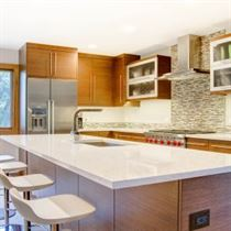 Remodeled kitchen with brown cabinets and island with white counter tops and floor with tile walls