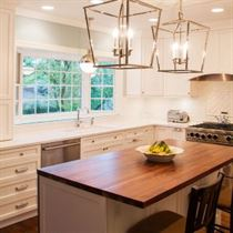 Kitchen remodel with white cabinets and brown floor and island