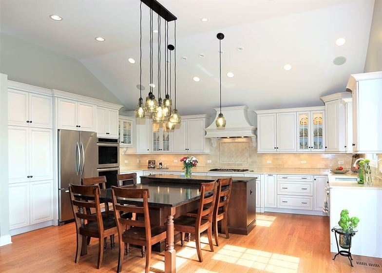 Kitchen remodel with white cabinets and brown floor and table