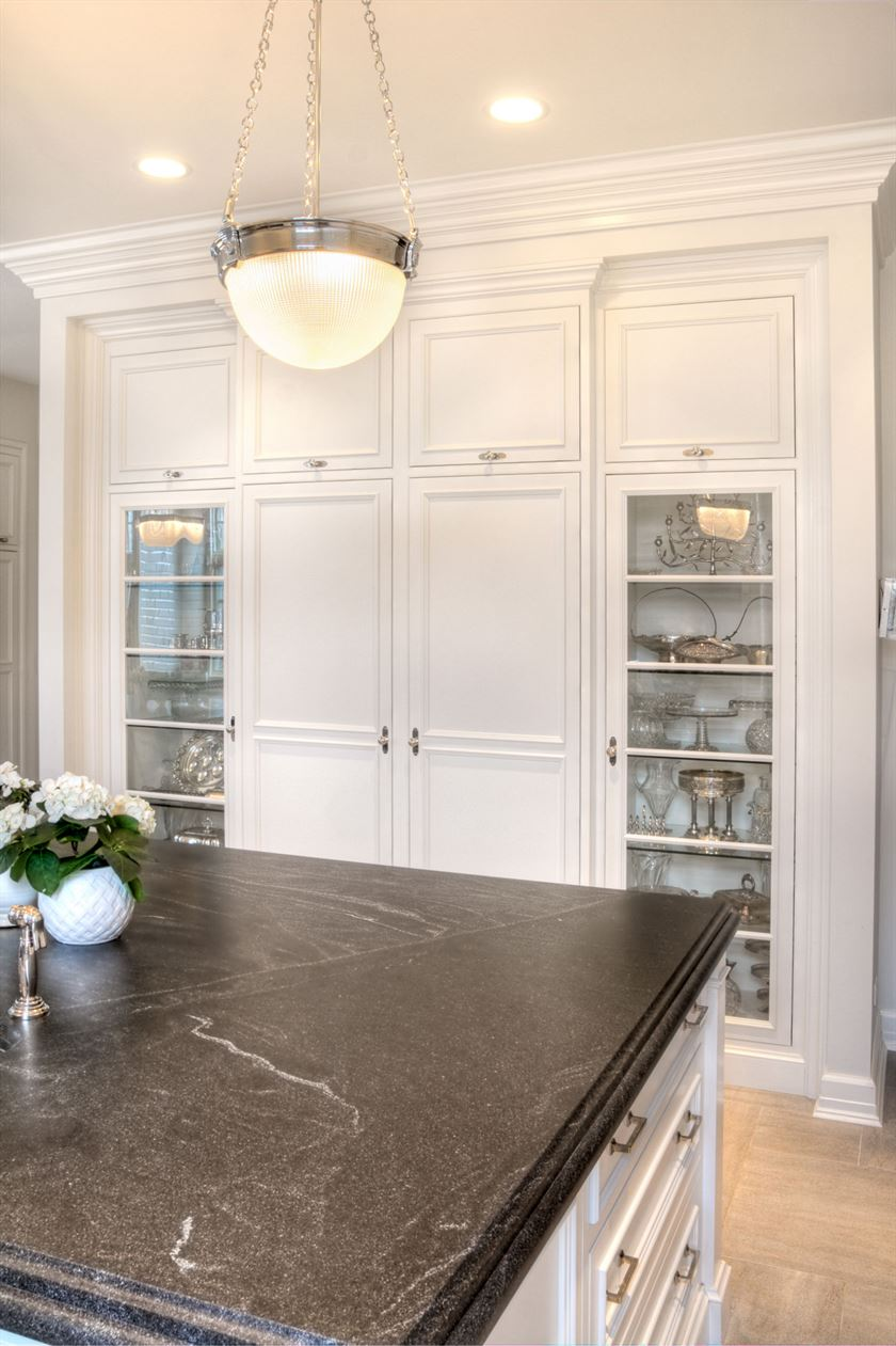 Remodeled kitchen with brown floor white cabinet and island with black counter tops