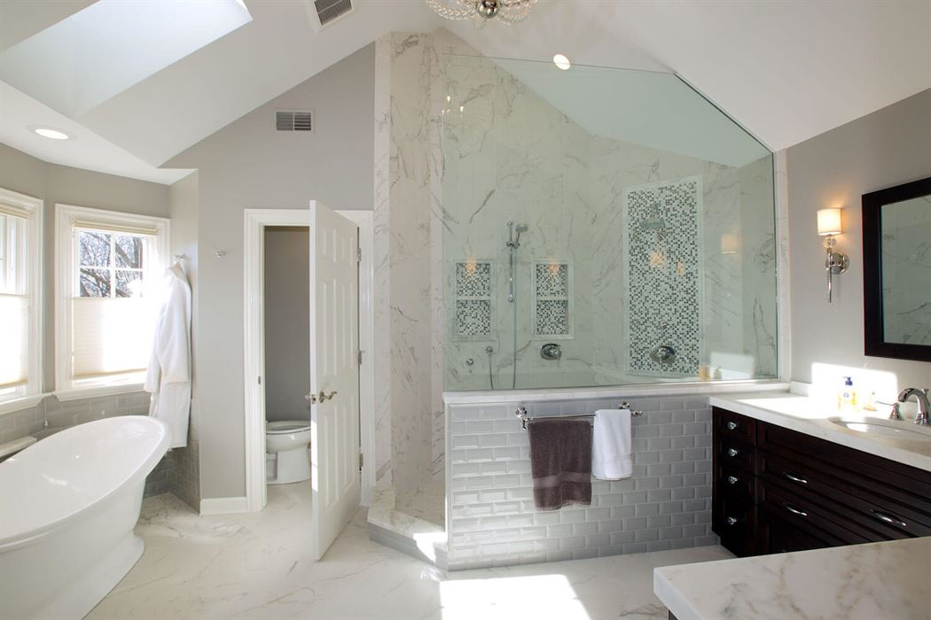 Bathroom renovation with white floor tub and walls with brown cabinets and tile shower
