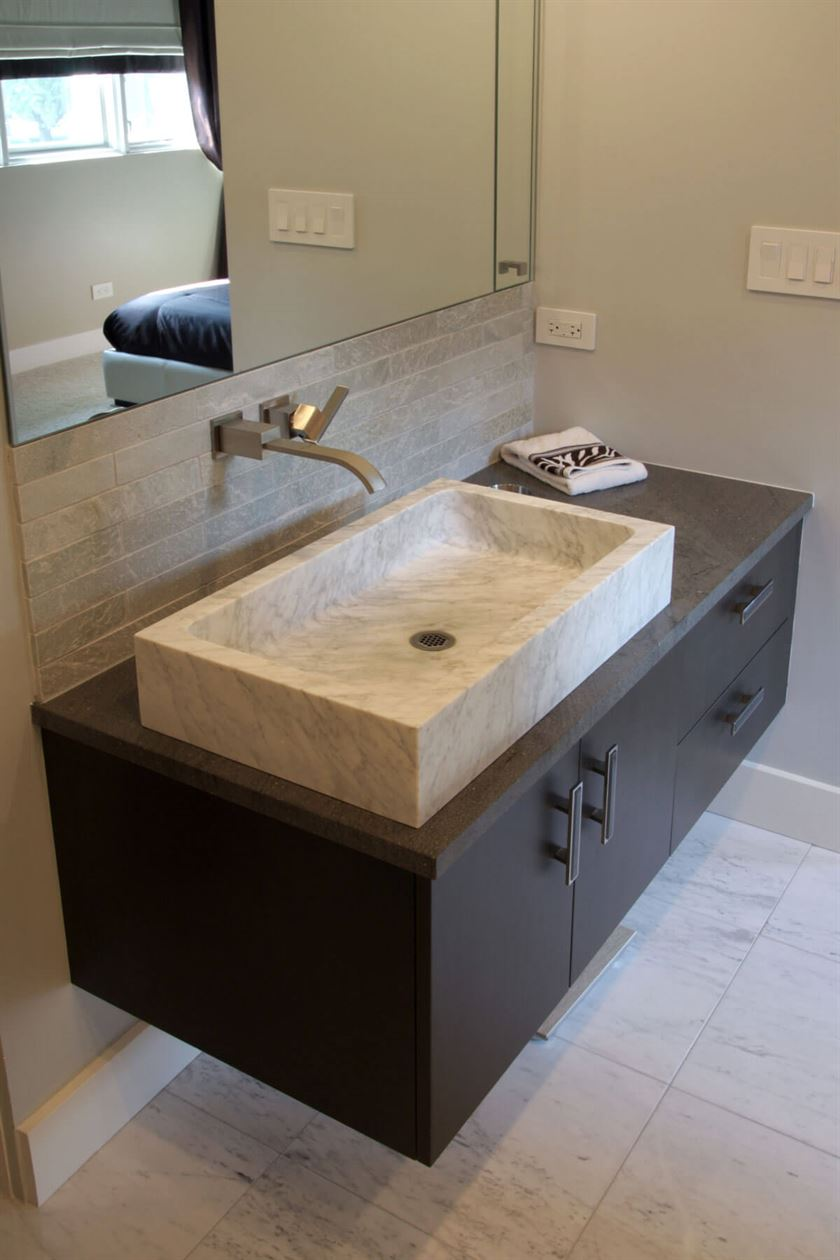 Redesigned bathroom with dark brown cabinets and beige floor wall and sink