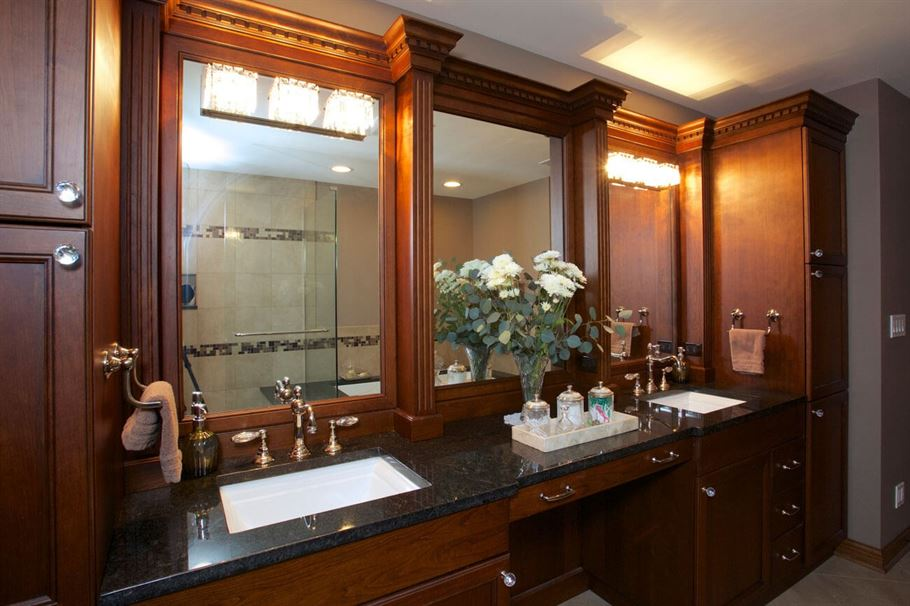 Bathroom renovation with brown cabinets black counter tops and gray walls