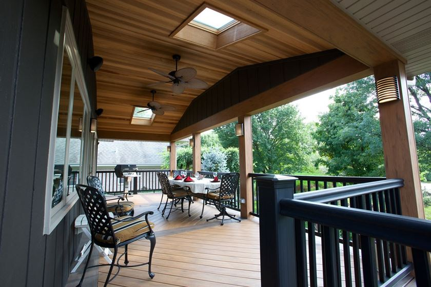 Porch design with black wood rail, brown wood floor, and brown wood ceiling