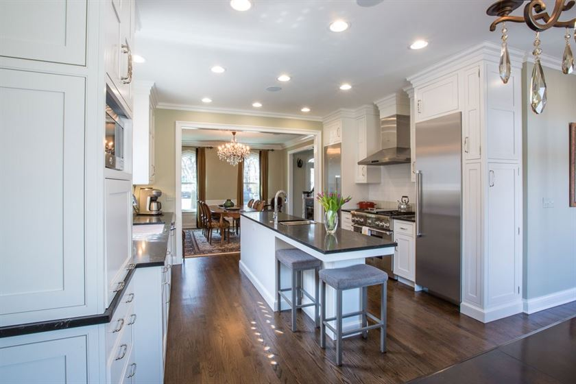 Kitchen Renovation with brown floor beige walls and white cabinets