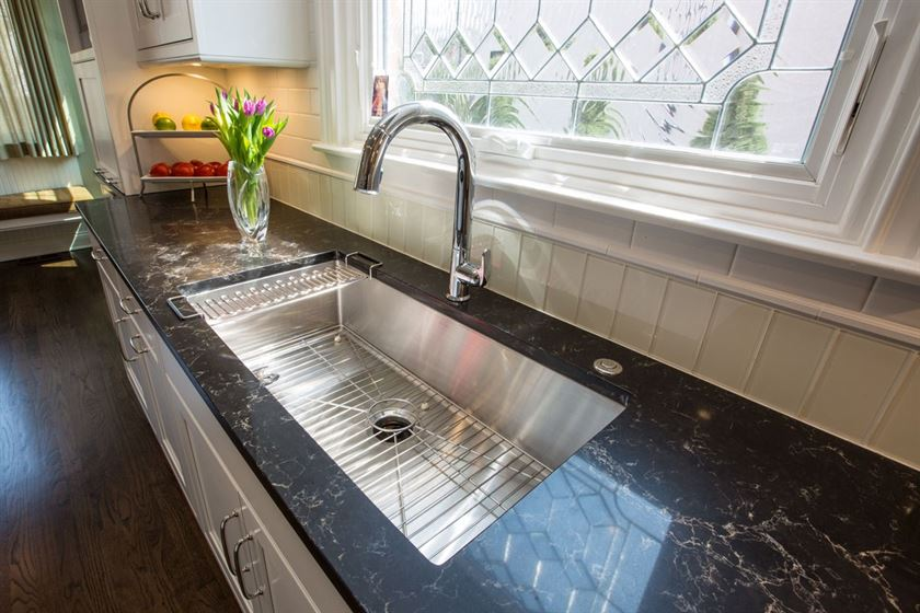Kitchen renovation with brown floor black counter top and white tiled walls