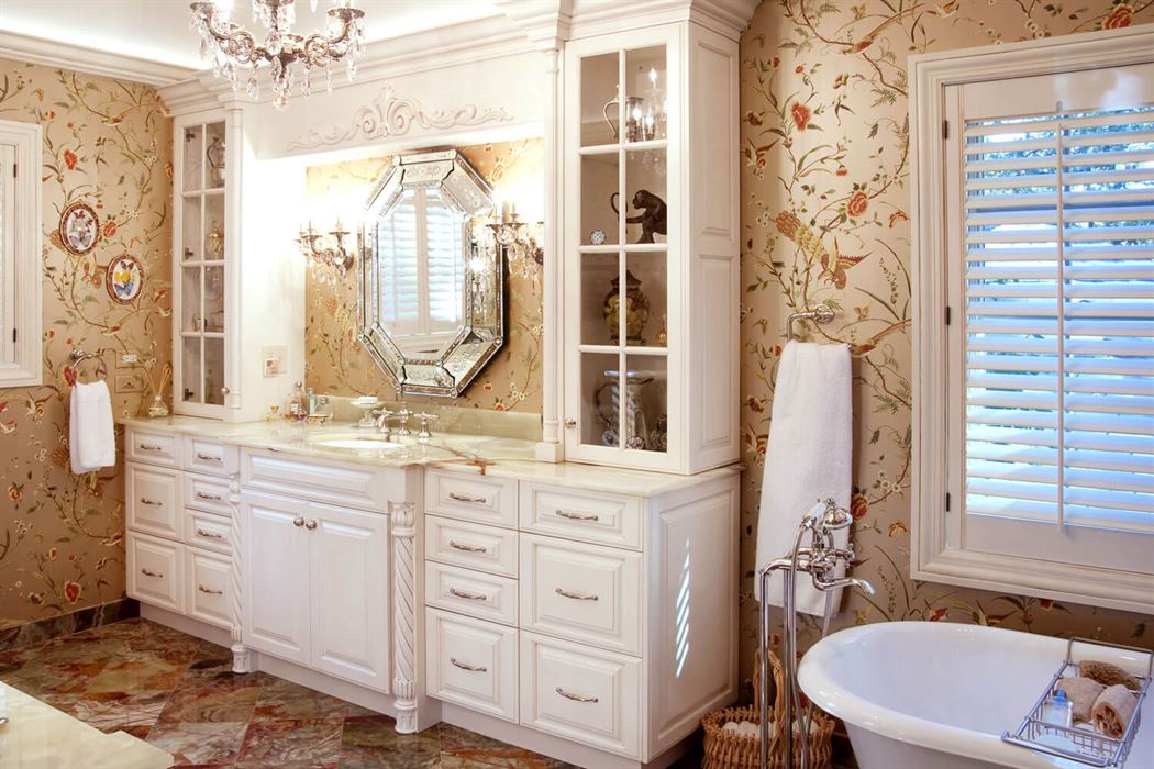 Bathroom renovation with patterned walls and floor with white cabinets and tub