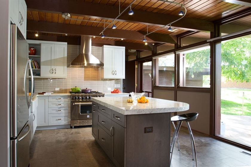 Kitchen renovation with white walls brown ceiling and dark brown island