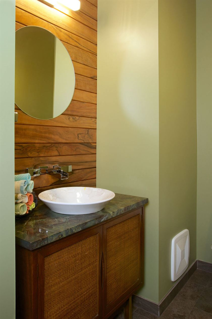 Redesigned bathroom with brown cabinets white sink and green walls