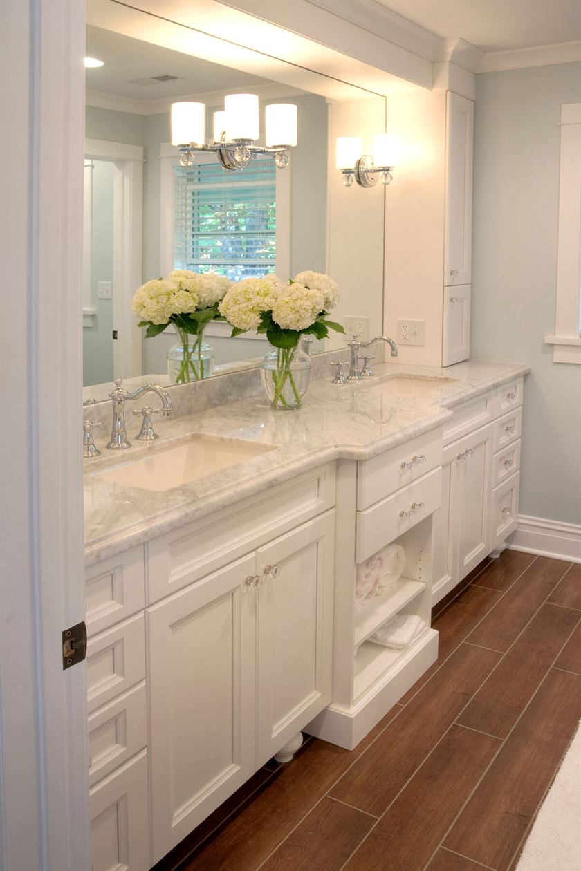Bathroom redesign with white cabinets and brown floor