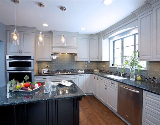 Kitchen remodel with brown wood floors, black island, white cabinets, and granite counter tops
