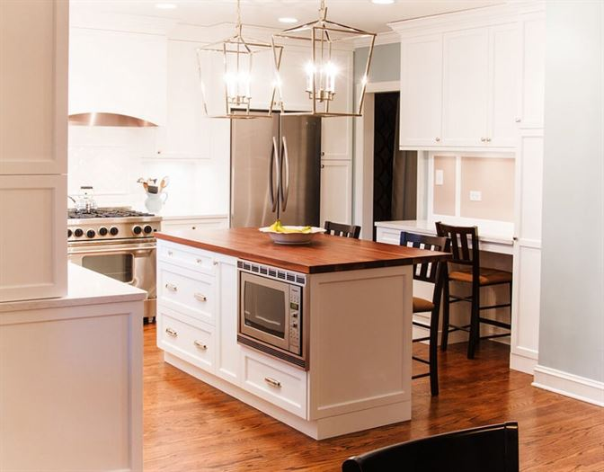 Kitchen remodel with wood floors, white cabinets, and a center island with storage and a microwave