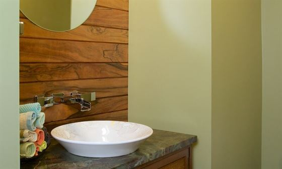 Renovated modern bathroom with wood accents and green walls