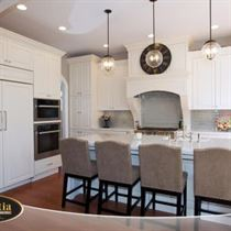 Kitchen remodel with white granite counter tops and sink, white walls, brown wood floor