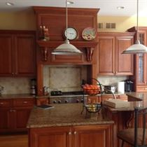 Kitchen remodel with brown wood floor and cabinets with patterned granite counter tops