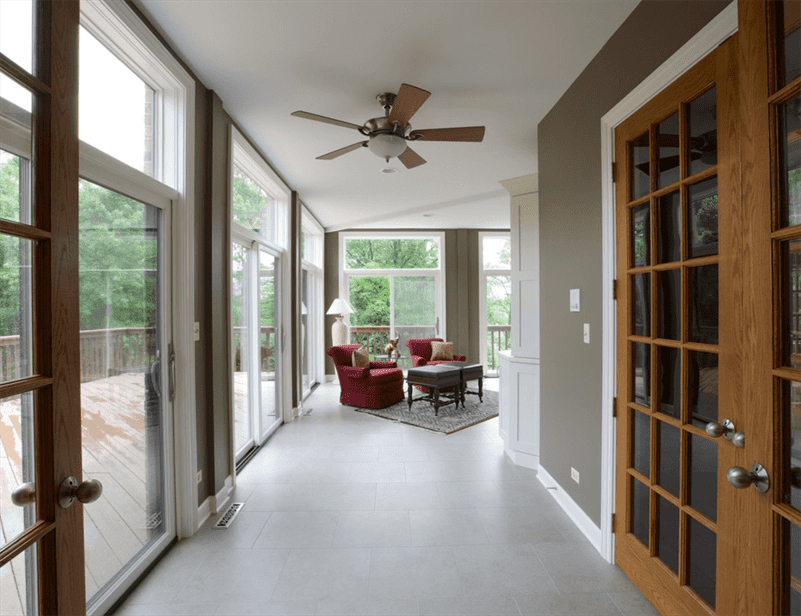 Living Room design with brown wood door, patio entry, white carpet, ceiling and entertainment center and gray walls
