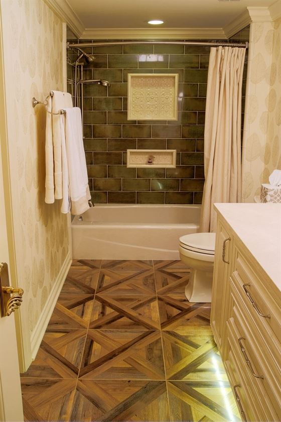 Bathroom renovation with brown flooring and beige cabinets and tub