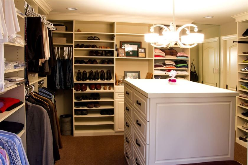 Remodeled walk-in closet with brown carpeting and white drawers
