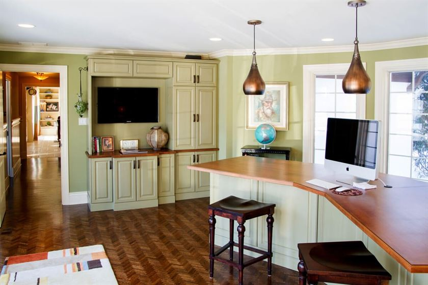 Remodeled kitchen with brown flooring and counter tops with beige cabinets