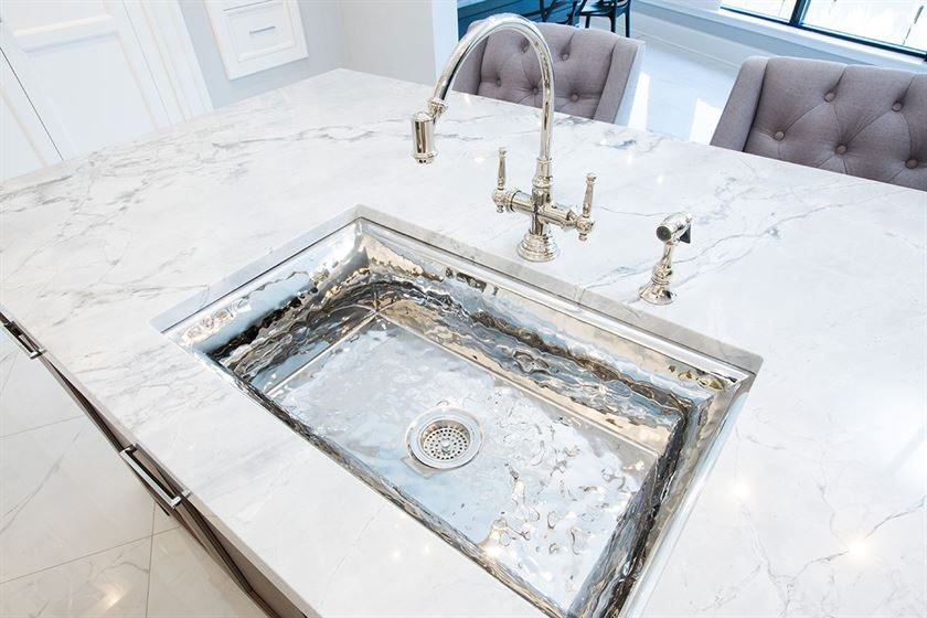 kitchen sink remodeling with white counter top and chrome sink