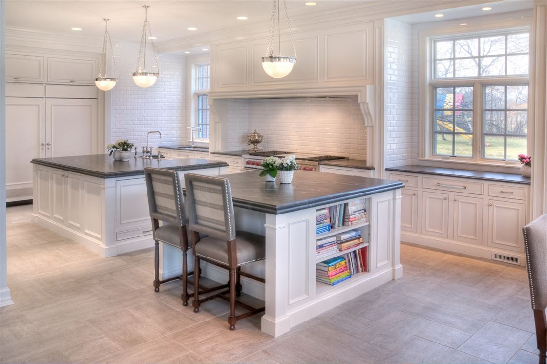 kitchen remodeling beige floor with white island, black counter tops and white walls