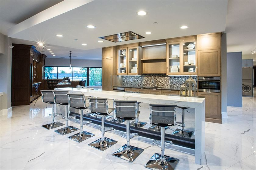 open concept kitchen showcase white floor with white island and brown cabinets