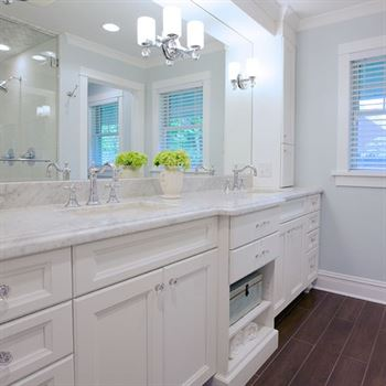 White bathroom with double sinks and chrome fixtures complement a dark wood floor