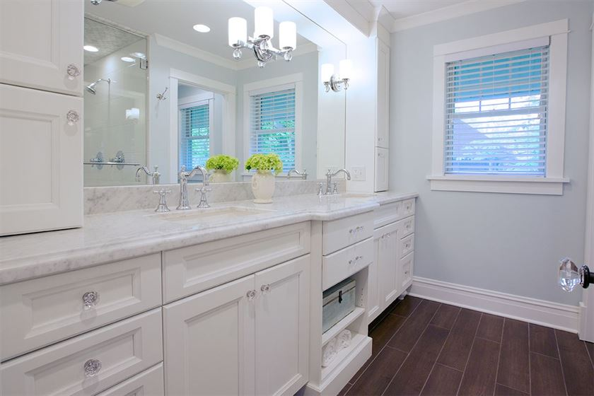 bathroom renovation with brown flooring and white walls and cabinets
