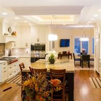 brown flooring with white counter tops and cabinets black island