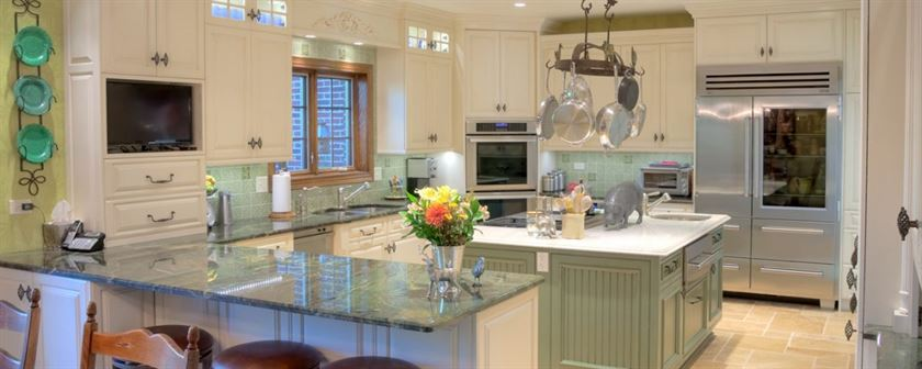 updated kitchen with green and white countertops and cabinets and a center island