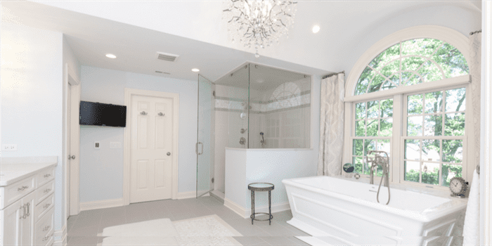Renovated bathroom with crystal chadelier, freestanding stub, and large stand-up shower