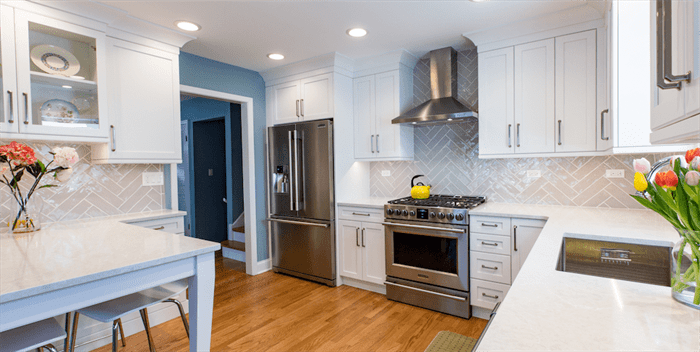 renovated kitchen with stainless steel appliances, wood floors, and white cabinets
