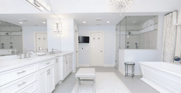 Updated modern bathroom with white cabinets and walls, a stand up shower, separate soaker tub, and a tv in the corner