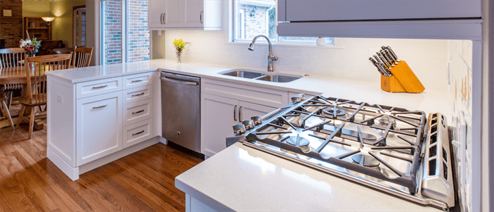Updated kitchen with new stainless steel stove, white countertops, stainless steel dishwasher, and wood floors
