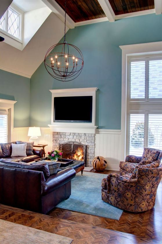 Living room with light blue walls and TV mounted over fireplace