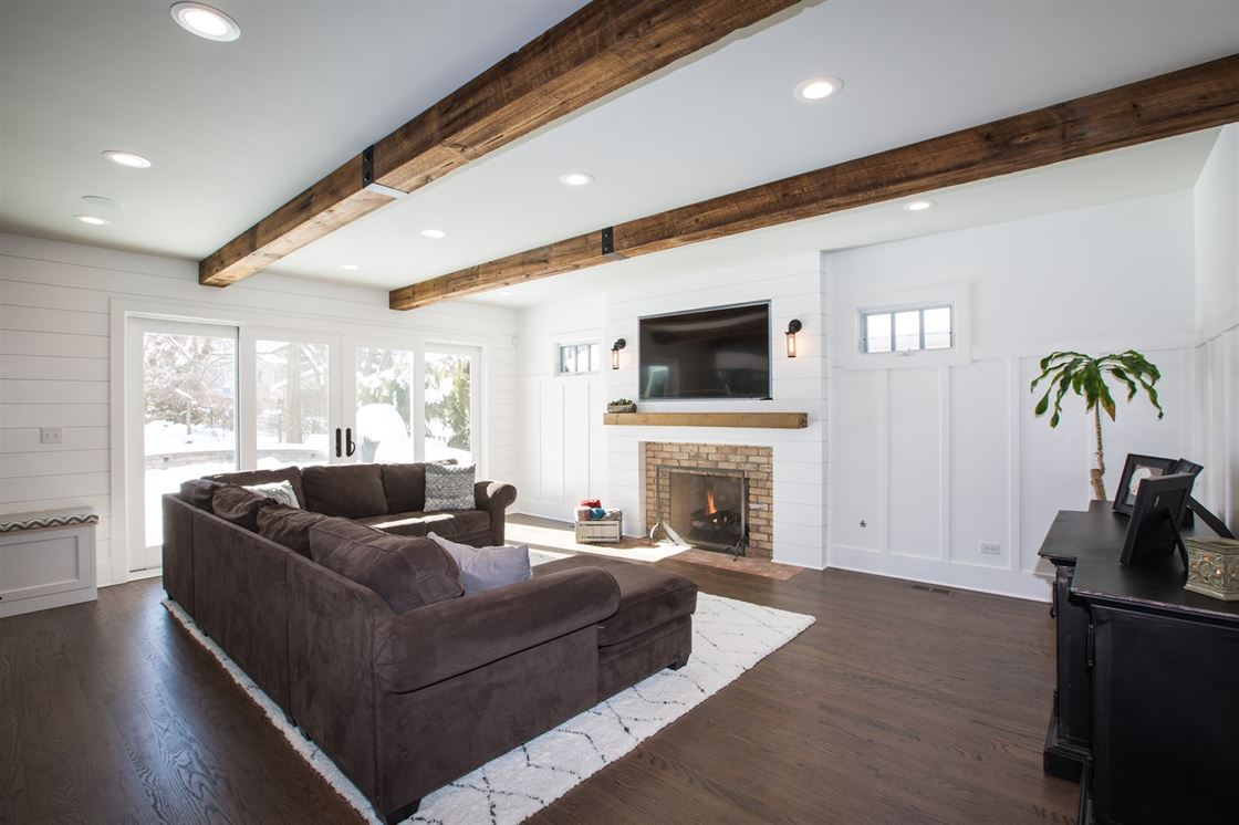 Living room addition with wood beams on ceiling and brick fireplace