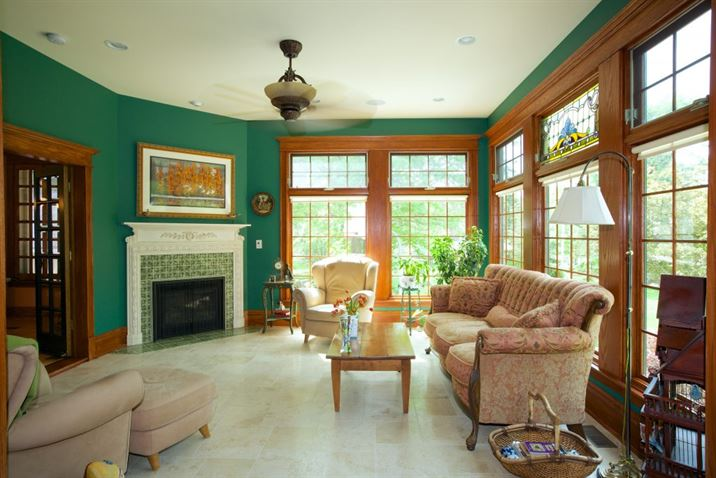 Living room addition with green walls, wood trim, and green tile on fireplace