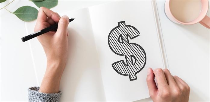 Woman drawing a dollar sign in a notebook
