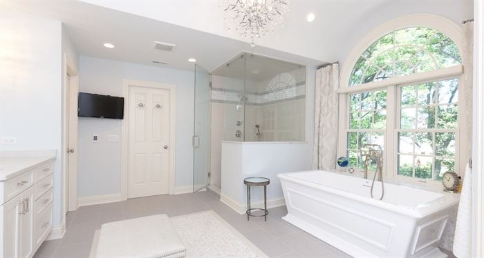 Renovated modern white bathroom with standalone tub and glass shower