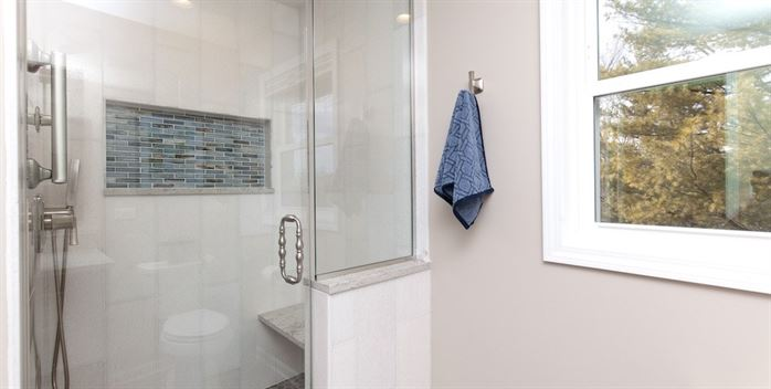 Renovated bathroom with walk in shower and shower seat