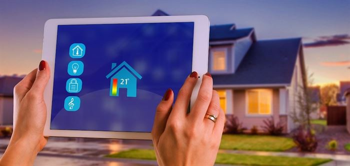 Woman holding iPad controlling the temperature of the house
