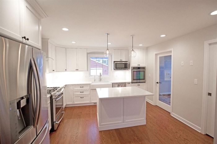 Renovated kitchen with wood floors and white island