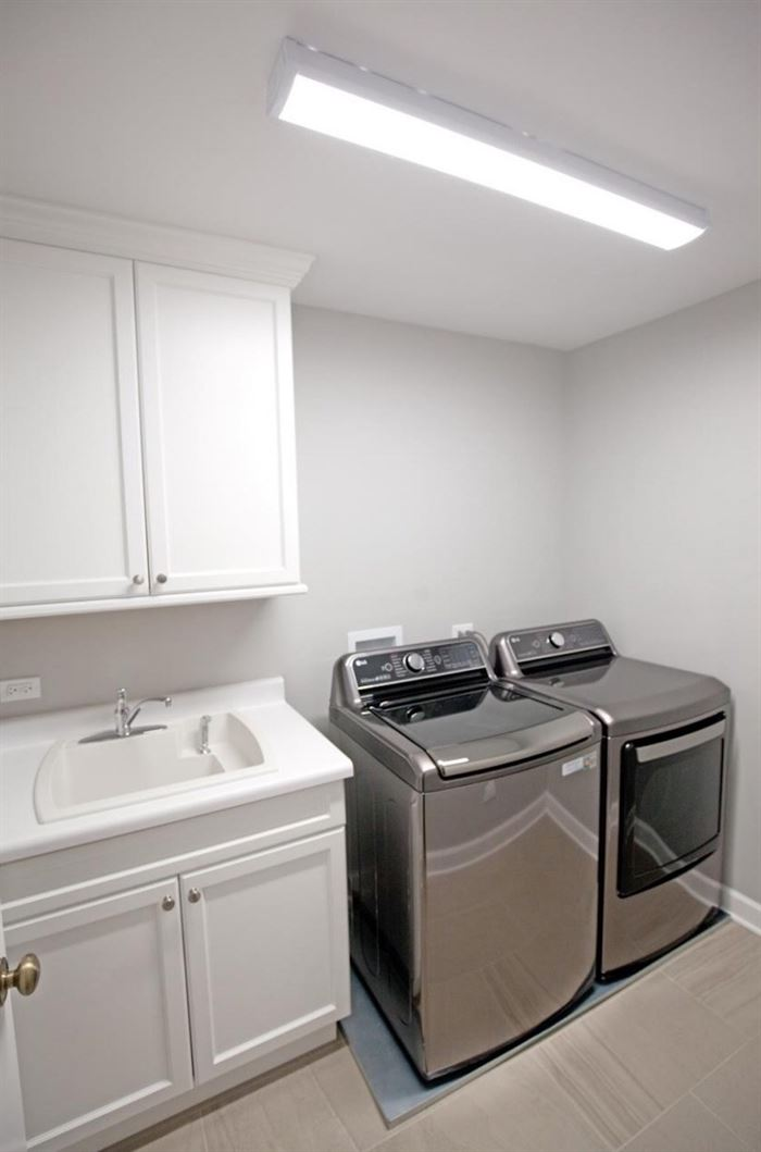 Renovated laundry room with side by side washer and dryer
