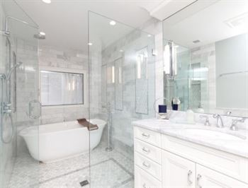 Marble bathroom with stand alone tub and white cabinets