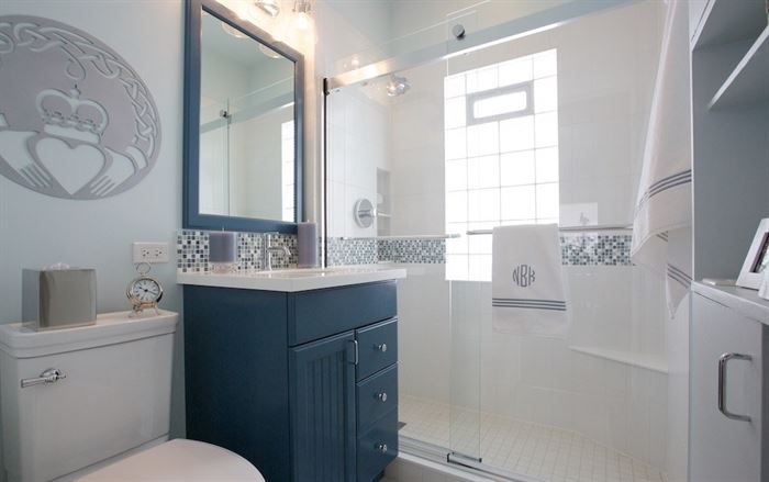 Blue and white bathroom with walk-in shower and claddagh symbol on the wall