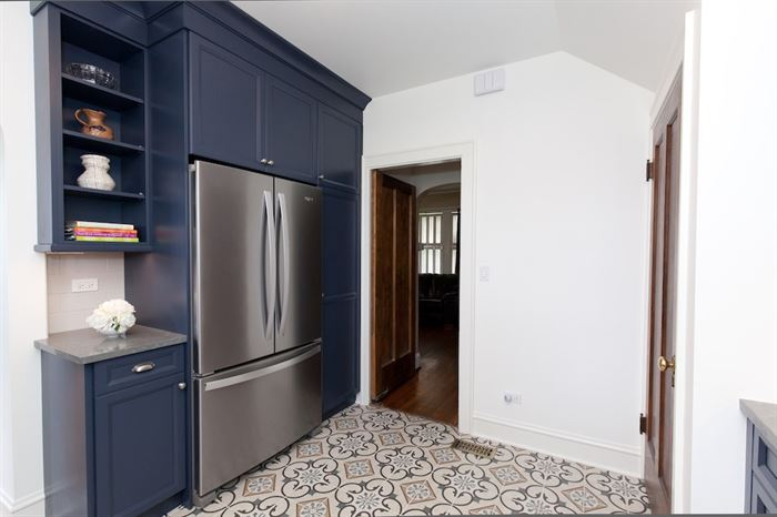 Completed kitchen remodel with blue lower cabinets cabinets around stainless streel fridge
