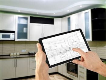 Person holding a tablet with a kitchen drawing in front of the renovated kitchen