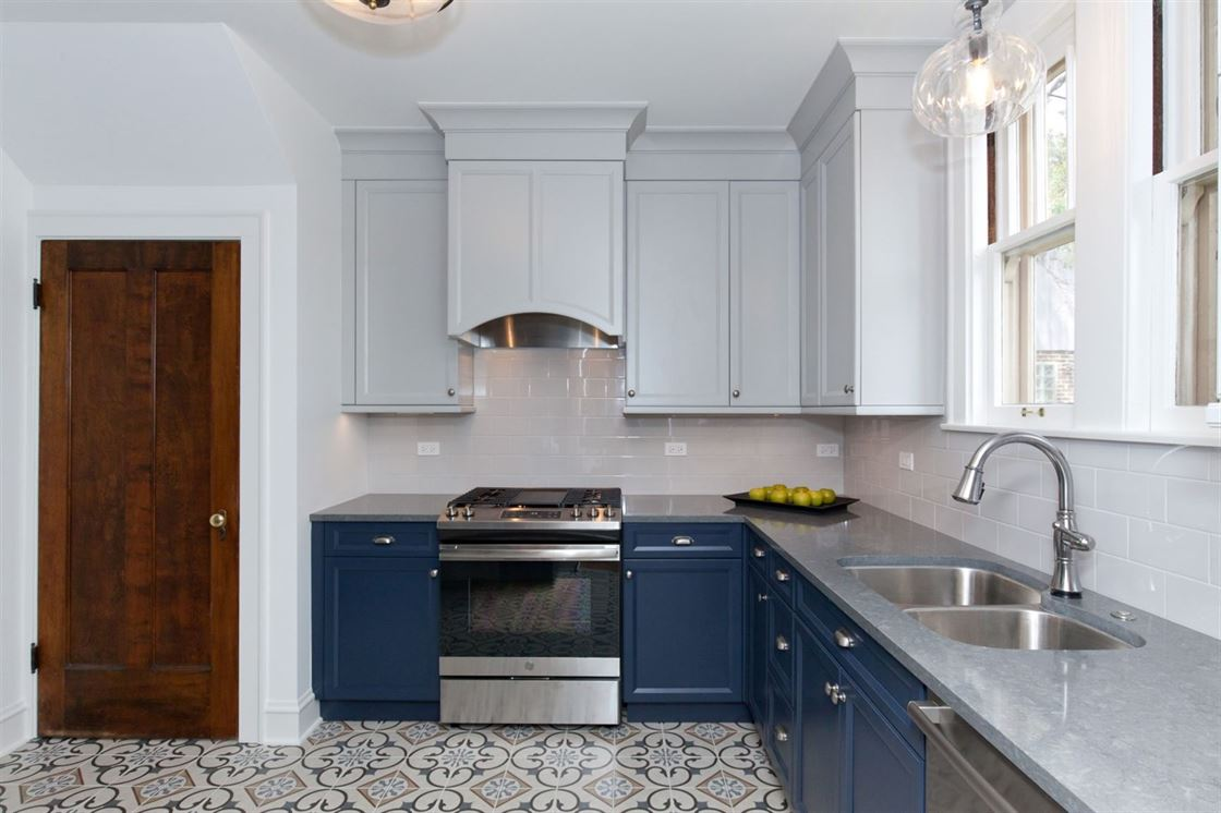 two-toned kitchen with patterned tile floor