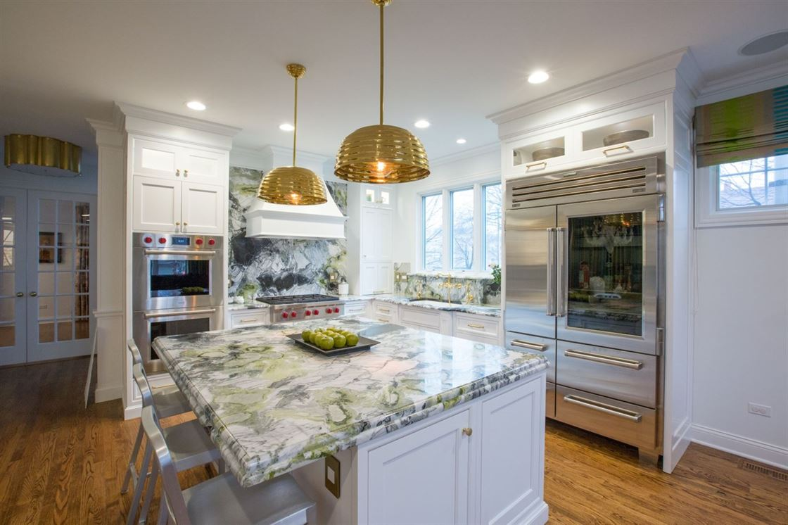 modern kitchen with granite backsplash and gold accents